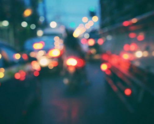 Autoverkehr in der Dämmerung mit blendenden Scheinwerfern